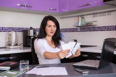 Stock Photo of stressed young woman is doing banking and administrative work holding bills a