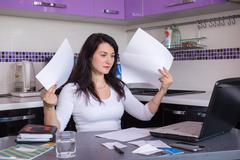 stressed young woman is doing banking and administrative work holding bills a - stock photo