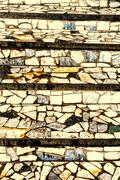 Different color cemented stone tiles create an abstract repeating pattern. - stock photo