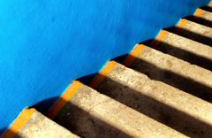 Blue smooth concrete and steps of aging yellow concrete creates a diagonal ab - stock photo