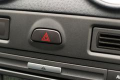 Grey unknown car dashboard interior with Hazard warning light symbol - stock photo