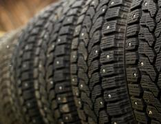 Single row of popular car winter snow tyres with metal spikes for better grip Stock Photos