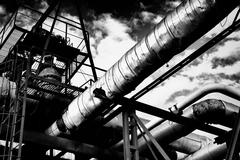 Metal industrial piping of a factory that carries water/gas/materials and met Stock Photos
