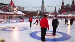 Players curling throw stones on the ice on Red Square in Moscow. Stock Footage
