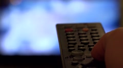 Hand changing channels on remote control, blur TV Stock Footage