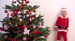 Stock Video Footage of Smiling child dressed in Santa Claus suit arrange Christmas ornament in tree
