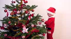 Stock Video Footage of Lovely Child dressed with Santa Claus suit arrange Christmas tree, waiting gifts
