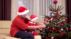 Stock Video Footage of Father and little son dressed in Santa Claus arrange Christmas tree