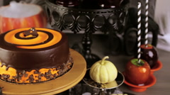 Table with colored candy apples and cake for Halloween party. - stock footage
