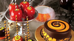 Table with colored candy apples and cake for Halloween party. Stock Footage