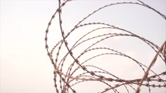 Cinematic move along barbwire fence into the sea Stock Footage