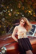 Stock Photo of stylish woman standing with a retro car in fashion dress