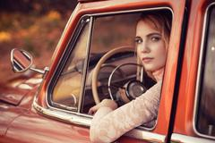Stock Photo of beautiful woman sitting in red retro car