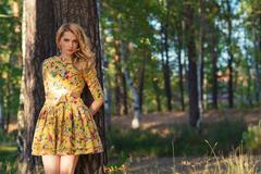 Young woman in a yellow dress in the park Stock Photos