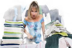 Woman ironing on ironing board many clothes Stock Photos