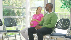4K Friendly doctor talking to couple who are expecting a baby Stock Footage