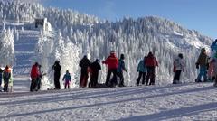 Tourists preparing to ski on slope, mountain resort, winter landscape Stock Footage