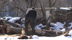 Man cutting wood with chainsaw in winter Stock Footage
