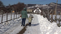 Mother and child walking back home on village road with snow in winter scenery Stock Footage
