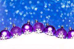 christmas purple balls in snow on blue glitter background - stock photo