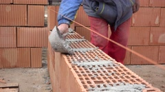 Stock Video Footage of Worker spreading the mortar on masonry bricks, build wall