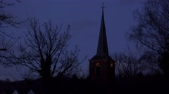 Old medieval rustic church belfry tower with clock in the night - stock footage