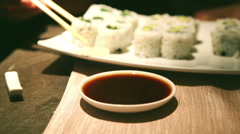 a close up of man eating with chopsticks sushi vegetarian roll - stock footage