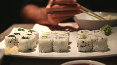 man eating sushi and rice in a bowl with chopsticks - stock footage