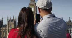 Attractive tourist couple taking photo on a smartphone and discovering London. Stock Footage