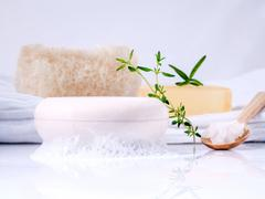 Herbal spa soap bar on white bath towel with thyme,rosemary and luffa isolate - stock photo