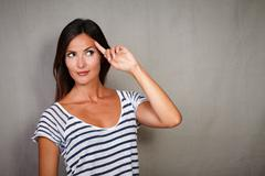 Pensive lady planning with hand on head while standing against grey texture b Stock Photos