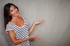 Charismatic lady 30-34 years old in casual clothing pointing against grey bac - stock photo