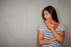 Shocked woman in casual clothing looking away from camera - copy space Stock Photos