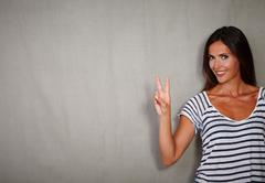 Good-looking woman celebrating with victory sign while standing - copy space - stock photo