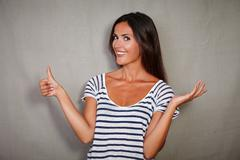 Brunette youngster standing with thumb up while toothy smiling at camera - stock photo