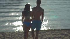 The couple (pair) walk on the beach and hug by the bright sunlight reflection Stock Footage