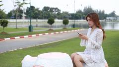 Women sharing social media in a smart phone at public park Arkistovideo