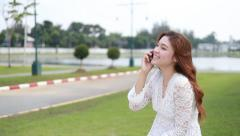 Woman calling on the mobile phone in public park - stock footage