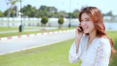 Woman calling on the mobile phone in public park Stock Footage