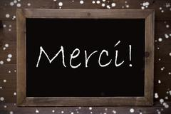 Chalkboard With Merci Means Thank You, Snowflakes - stock photo