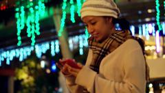 Video of Asian girl using smart phone during holiday season with christmas light - stock footage