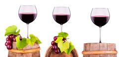 Glasses of red wine on a wooden barrel with grape Stock Photos