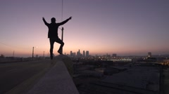 Man Stands with Arms Raised While Sun Sets Over Los Angeles City - stock footage
