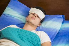 Young sick or unwell man in bed Stock Photos