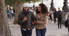 Young beautiful African American couple walking through an urban city. Shot on R - stock footage