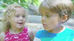 4K Happy little boy & girl in the woods, little girl whispers a secret in boy's  - stock footage