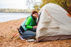 woman crawls into tent - stock photo