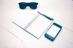 cellphone with notepad and pen vintage style - stock photo