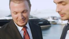 Two businessman communicate using a tablet computer in a sea cargo port Stock Footage