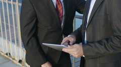 Stock Video Footage of Two businessman communicate using a tablet computer in a sea cargo port